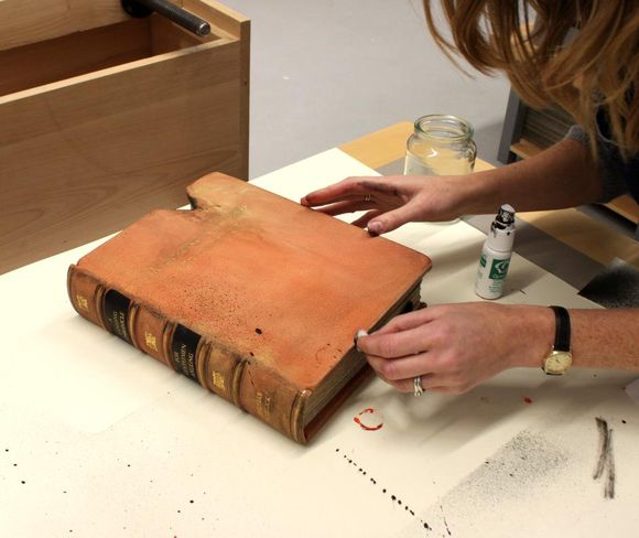 The book rests on a table as black paint is dripped and sprayed onto the leather to create a worn look.