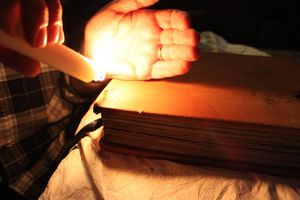 Someone holds a lit candle to the leather to burn the edges of the book.