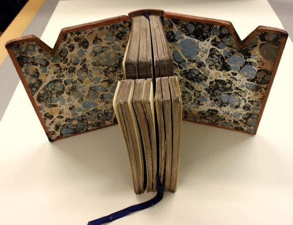 The book stands upright on a table with the boards opened out, showing the marbled paper in tones of blues and creams.