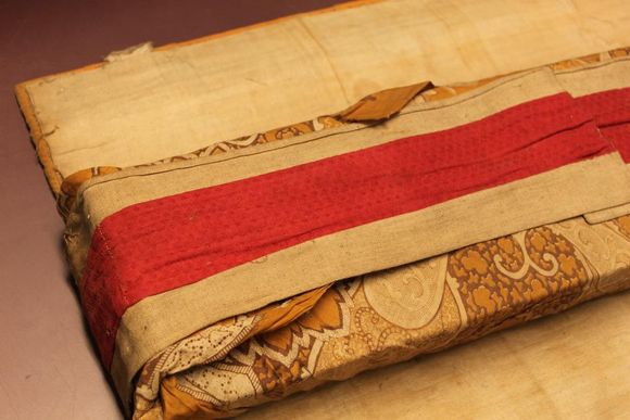 A manuscript wrapped in cotton. There is a patterned yellow fabric covering the manuscript with a swirling, floral motif. Around that is a strip of white and red fabric.