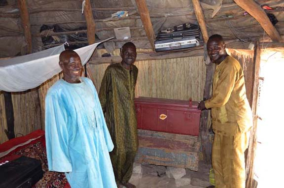 Inside someones home, the walls are med from reeds. Three men smile and look very happy. Two of them stand by a metal trunk.