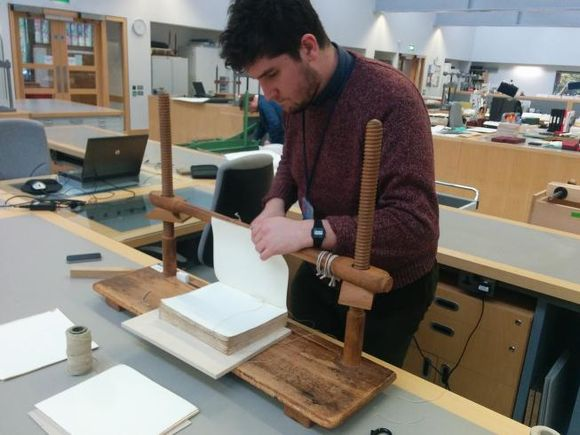 Rob Sherman stands at a sewing frame, sewing a textblock together. The sewing frame is made of wood.