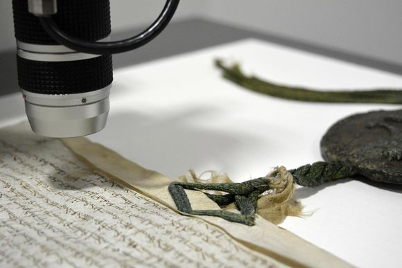 A up-close shot of the Magna Carta under a magnifier. Part of the charter is visible in the image along the wax seal.