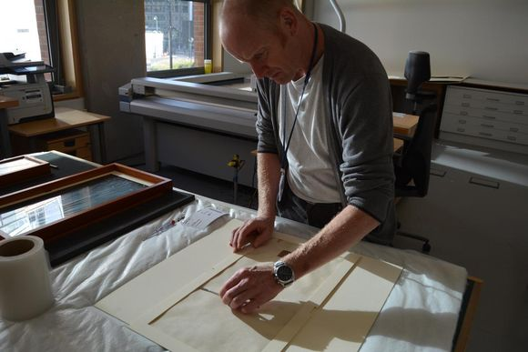 The item rests on a soft surface while Gavin inspects it. The charter is house in cream mount board.