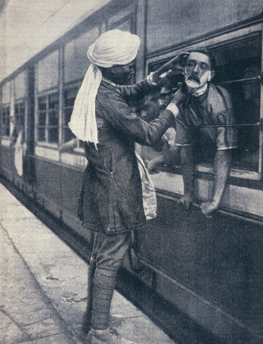 Army officer leaning out of the train window to be shaved during a stop