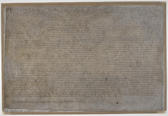 A full view of Magna Carta 1215. It is a rectangular pieces of parchment with small text.