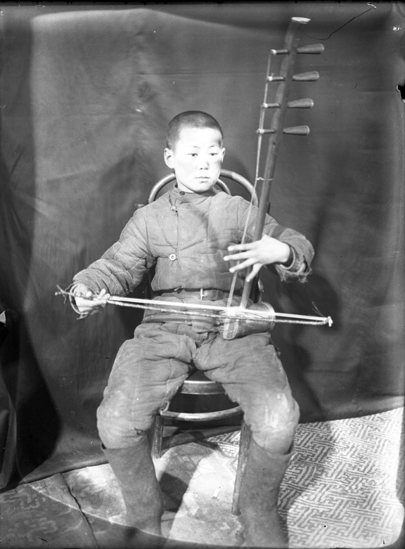 A young boy playing the huuchir