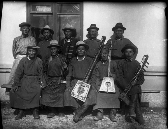 A group of ten musicians. The back row is standing and the front row seated, showing their various instruments.