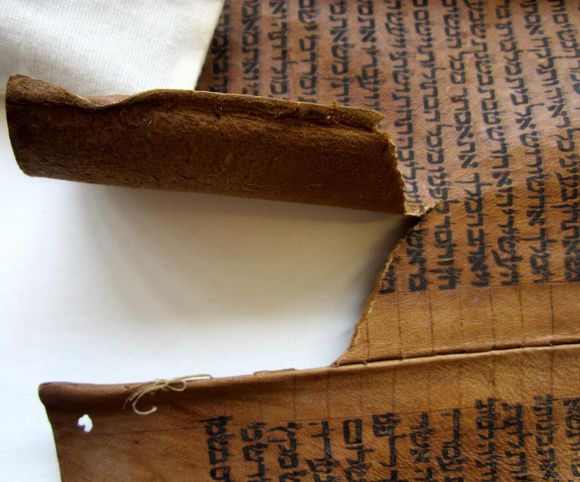 Two pieces of parchment are held together with sewing. In this image, along the left hand side, the sewing has broken and a large tear has developed in the scroll.