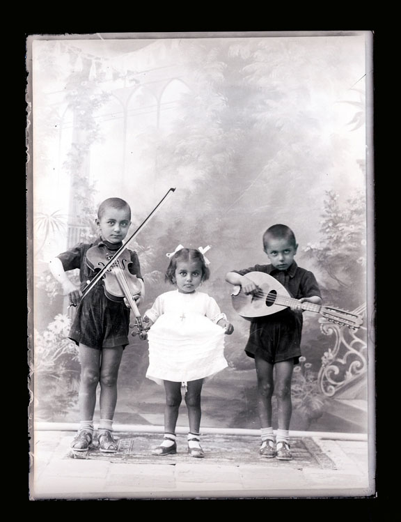 Studio portrait of three children. The two boys play musical instruments (violin and lute) the younger girl in the middle, holds the side of her dress possibly to show a dancing pose.