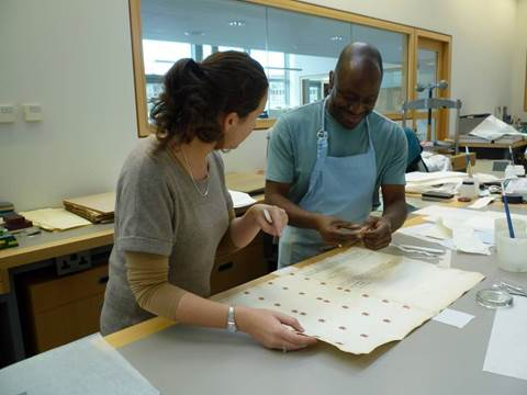 Two conservators look at a paper-based collection items at a bench, surrounded by conservator tools and materials like paintbrushes, paper, and paste.