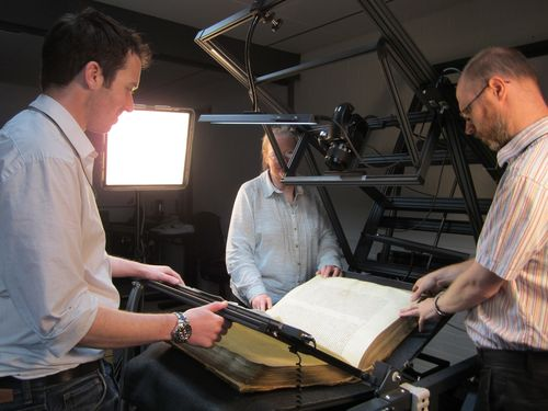 Three people stand around the large volume helping during the digitisation process.