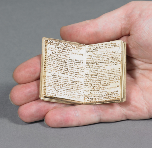 A hand holds a tiny book.