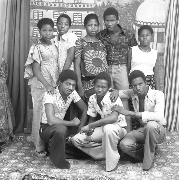 Group of young men and women wearing both African print and 1970s fashion.