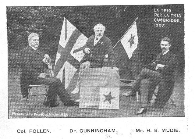 Photograph of John Pollen, George Cunningham and Mudie seated at a table with British and Esperanto flags