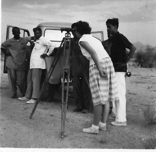 Madeline Morris looking through a surveyor's theodolite