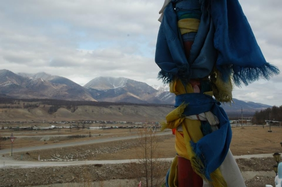 A prayer pole in the foreground. Mountains and the steppe in the distance.