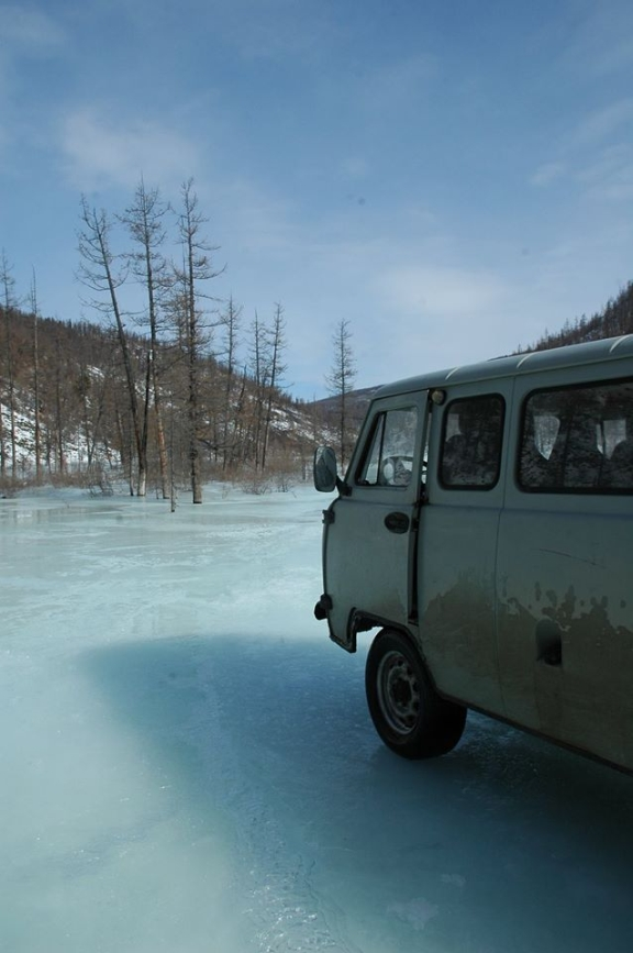 A camper van drives on the frozen river.