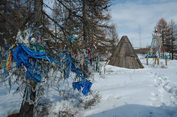 Prayer flags and scarves tied to trees. A conical hut is also visible among the pine and snow.