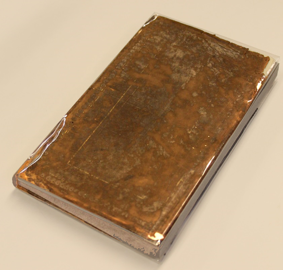 The cover rests on a table--it has been wrapped in polyester and a support made of foam has been inserted to mimic the measurements of the original textblock.
