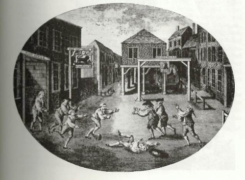 Men playing football in an empty market-place, one of them knocked to the ground