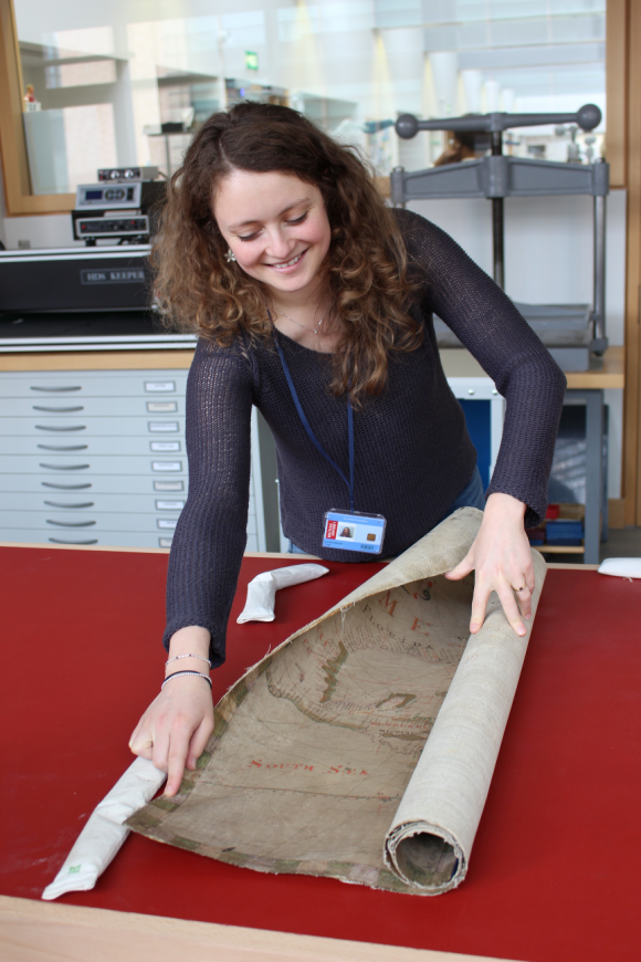 Camille stands at a desk and starts to unroll a large rolled map.