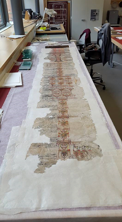 The manuscript lies on a table during the infill process.