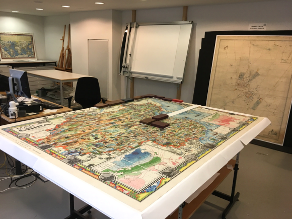 A large colourful map of China rests on a table during the mounting process.