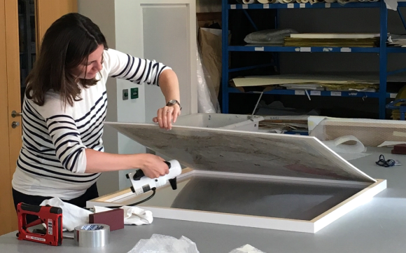 Conservator Lizzie lifts a map out of its frame while removing dust from the Perspex.