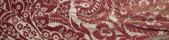 a closeup of a textile piece, with various flowers and leaves in red, atop a gold background.