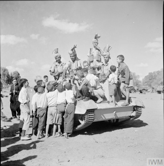 Local children play with Indian troops manning a Bren gun carrier, 13 November 1941