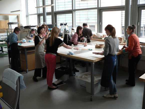 Nine Consevators are gathered around two tables in a studio, with various tools on the tables. Most conservators are wearing aprons, and some people are brushing down items on the desks with large soft Japanese brushes.