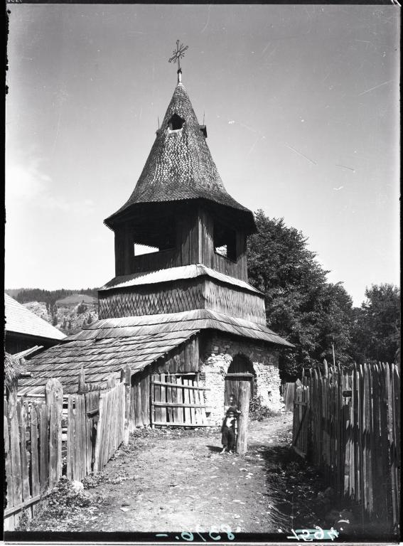 Photograph of a village with stone and wooden tower.