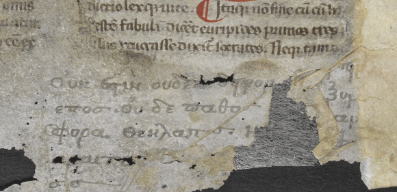 Formerly hidden areas of parchment have now been exposed during treatment. This section shows a portion of the latin text, in black, with a bold red capital. Underneath the text box is a partial handwritten notation in Greek, in now faded black ink.