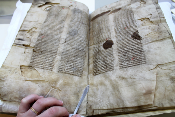 A hand with a metal conservation flat spatula tool, is gently removing the sewing from the manuscript, showing as a white thread. The manuscript is lying open on its supports. The damage to the parchment can be seen in the many tears and creasesm as well as ink stains obscuring some text.
