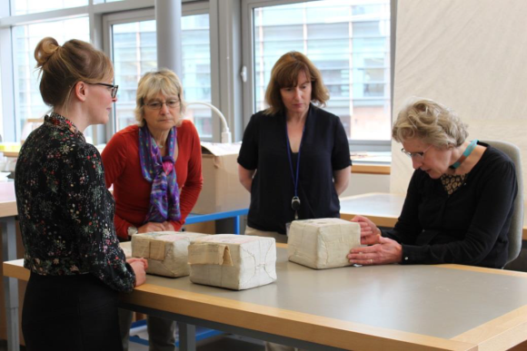 Curators look on as textile conservator Liz Rose inspects one of three parcels.