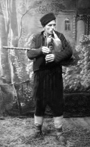 Studio photograph of a man posing with a bagpipe.