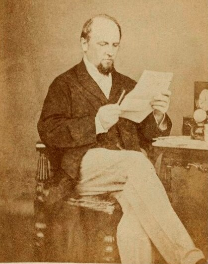 Photograph of Charles John Canning sitting with his legs crossed reading a document