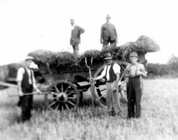 Agricultural labourers at Oxborough 1930s standing by a cart, with pitchforks