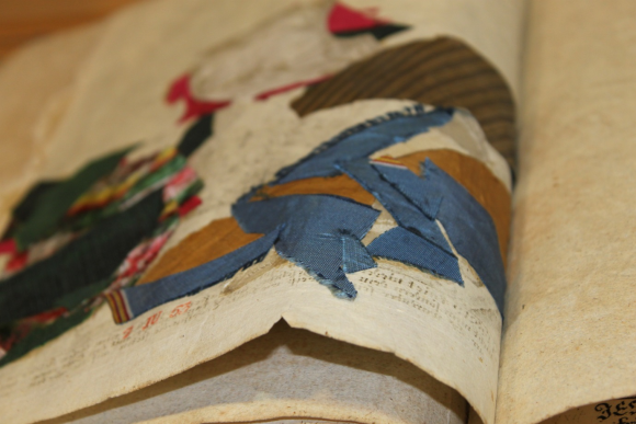 The same image, this time shown from the reverse of the page. The scraps of textiles of various colours including blue and brown, are often superimposed over each other.