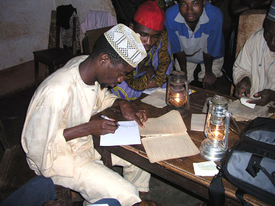 Young man copying Bamum script from a notebook.