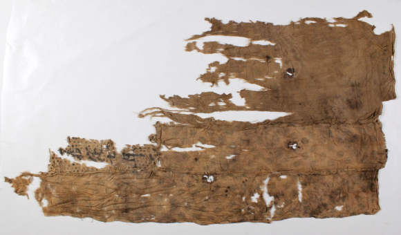 The reverse side of the Silk bundle, now completely unravelled and lying flat, after conservation work. The bundle is longer at the bottom, with most of the left hand side of the fragment missing. There can now be seen some characters superimposed on a series of stars on the bottom left hand side. There are also various holes in the silk.