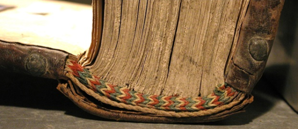 A close-up picture of a book, placed on its side, displaying a multicolored twined end-band, with blue, red and white.