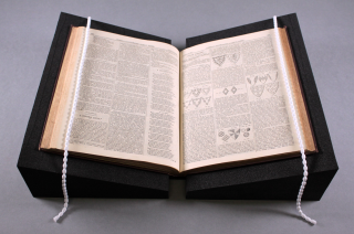 A picture of a book, lying open on two black foam supports, with white snake weights running down on the outer edge of the book pages.