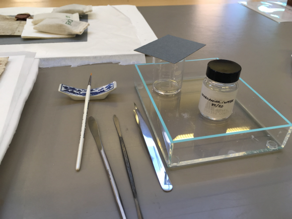 a picture of the variety of tools utilised in the charter rehousing. On a grey table rests two small metal spatulas, next to a shiny small sharp ended tweezer, and a small white-handled paintbrush, resting on a china paintbrush holder. To the right of the tools is a clear glass open box, with a small clear empty beaker, and a very small bottle of the chemical mixture which is clear in colour.