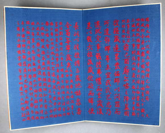 A Large folio opened out, of blue pages with red Chinese calligraphy neatly running down both pages in silk. The pages are thinly bordered in white material.