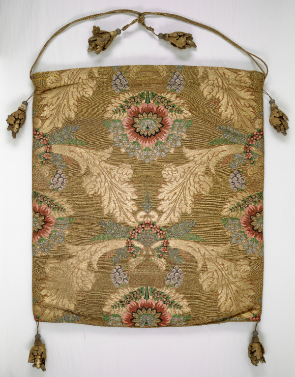 A large square silk brocade bag, with twin thin golden twine handles, ending in gold oak leaf bunches. The silk bag is deocrated with a central flower in pink, green and white, surrounded in a vaguely circular patter by large curling leaves, which in themselves are superimposed by small bunches of flowers in purple and pink, with green leaves. The background colour of the bag is a olive green in horizontal lines.