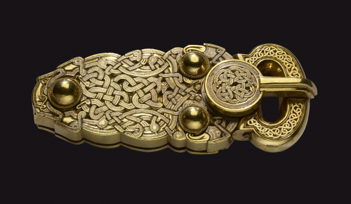 A gold buckle, intricately decorated with a web of snakes, predatory birds and long-limbed beasts.