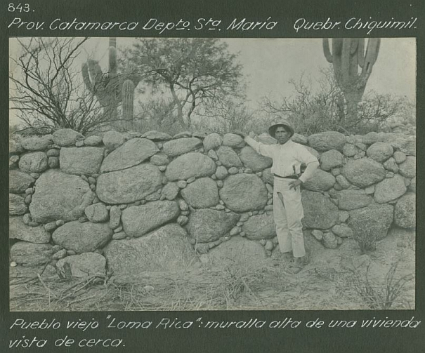 Black and white photograph showing a man standing by a stone wall, cacti grow along the upper ledge.