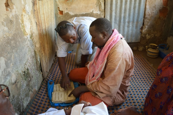 Dr. Fallou Ngom, looking over manuscripts with manuscript owner, El-hadji Lamine Bayo